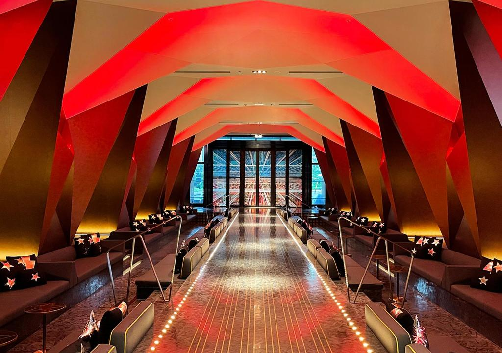 A red ceiling with tables and seats in public area of lobby