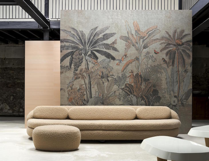 A wallcovering of palm trees infront of modern sofa and warehouse setting