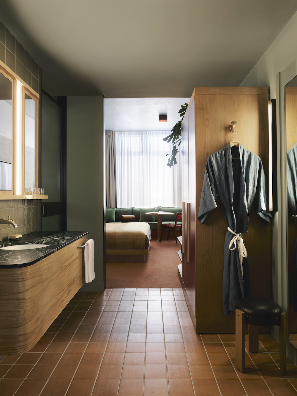An open, rustic bathroom leading into the guestroom
