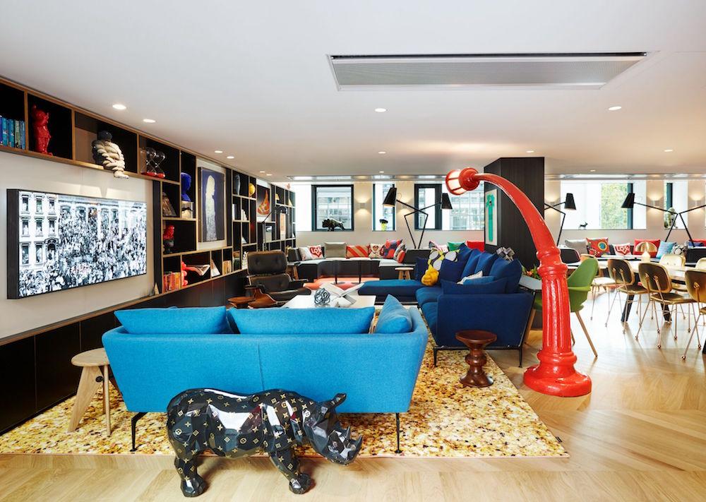 a blue sofa and red furniture inside citizenm in Paris