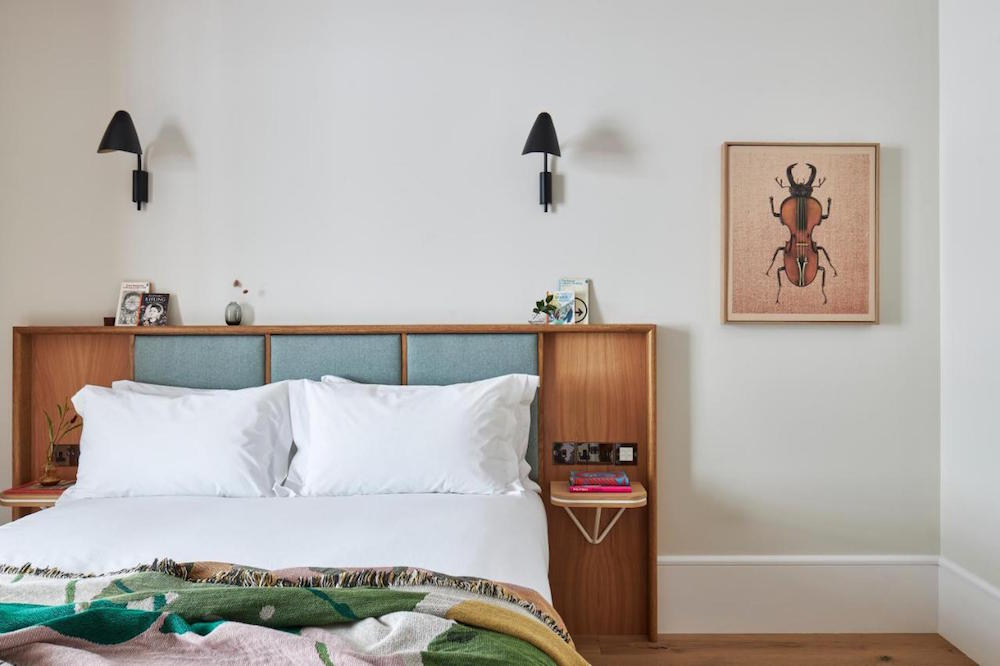 Hotel designs | A soft and contemporary bedroom, with wooden headboard and insect art