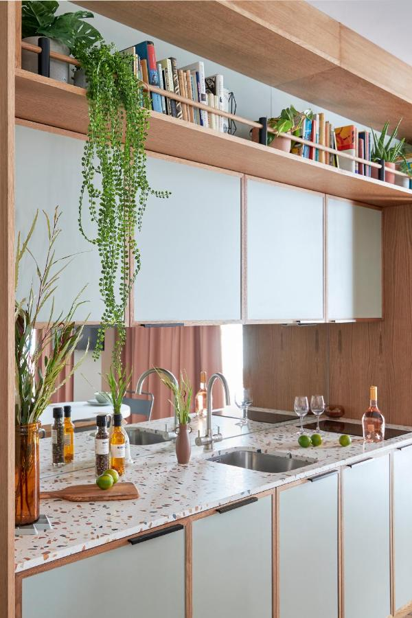 Hotel Designs | A bright, open kitchen area with terrazzo surfaces inside Turing Locke