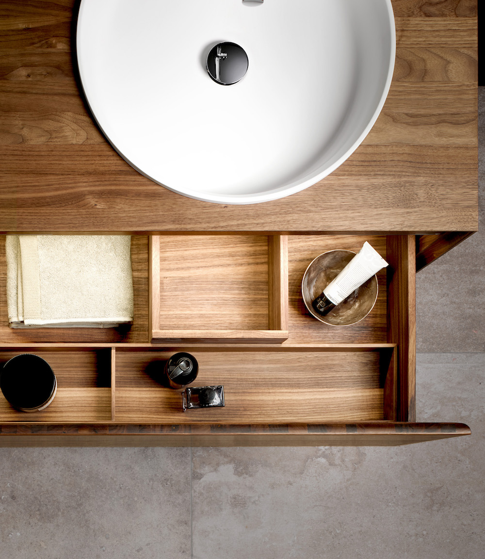 Close-up of wooden bathroom furniture draw open under a white basin