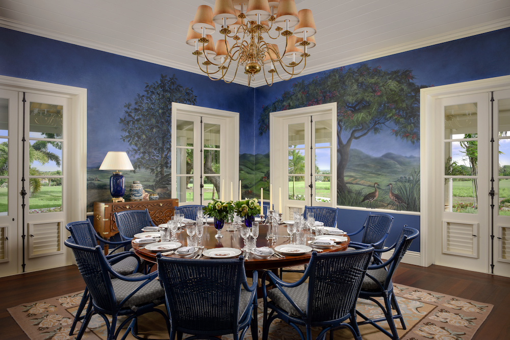 A blue dining room, which has paintings on the walls of trees